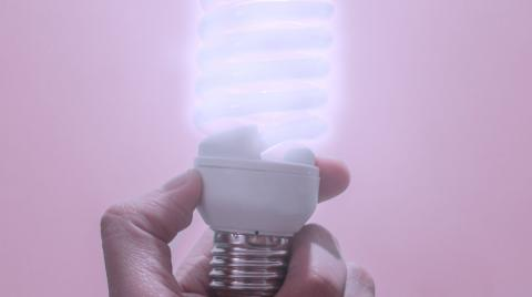 A hand holds up a lit low energy bulb.