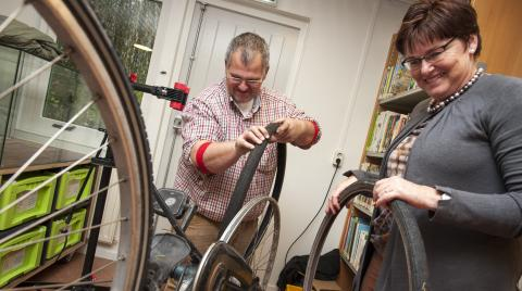 Man and woman at a repair cafe fixing a bike
