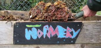 A gardener lifts a forkful of compost above a sign that says 'wormery'