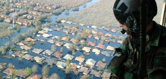 Soldier in helicopter overlooking flooded community