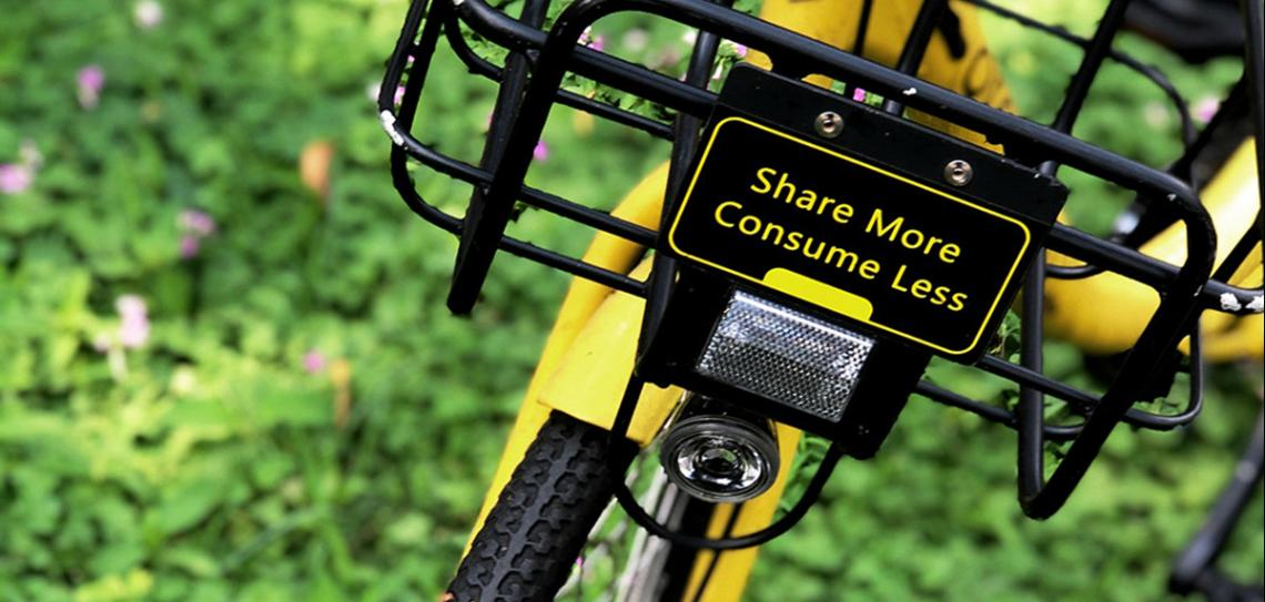 Yellow bike on green grass with a sign that says 'Share more, consume less'