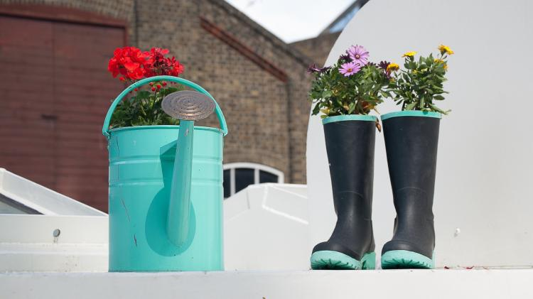 Watering can and old boots full of flowers on a white balcony