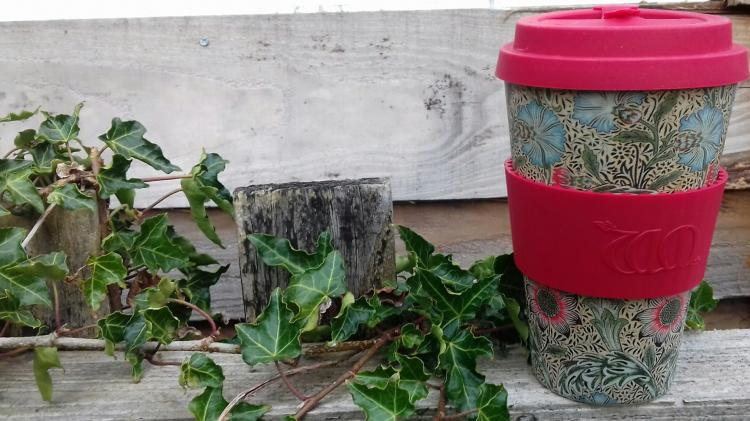 Reusable coffee cup on a wooden fence with ivy