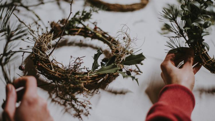 Two hands create festive wreaths out of branches