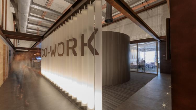 "An office environment with a wall that reads ""co-work""."