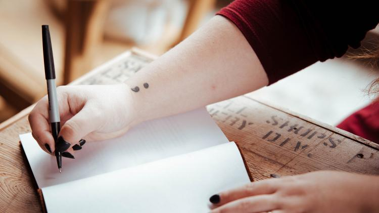 Person writing in a notebook with a semicolon tattoo on their wrist.