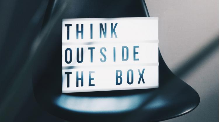 Light box saying 'think outside the box' sitting on a chair