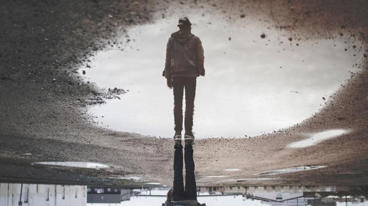 Person reflection in a puddle on the pavement